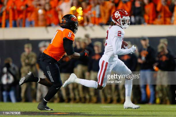 Wide receiver CeeDee Lamb of the Oklahoma Sooners runs for seven yards against linebacker Amen Ogbongbemiga of the Oklahoma State Cowboys in the...