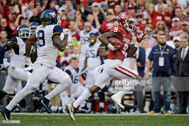 Wide receiver CeeDee Lamb of the Oklahoma Sooners runs past cornerback Elijah Battle of the West Virginia Mountaineers at Gaylord Family Oklahoma...