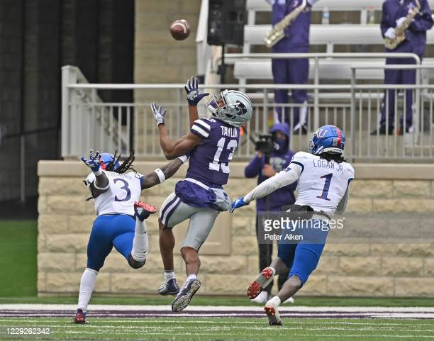 Wide receiver Chabastin Taylor of the Kansas State Wildcats makes an over the shoulder catch against safety Ricky Thomas of the Kansas Jayhawks and...
