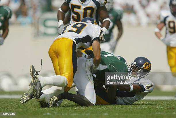 Wide Receiver Charles Rogers of the Michigan State Spartans is tackled by safety Bert Watts and cornerback Jemeel Powell of the California Golden...