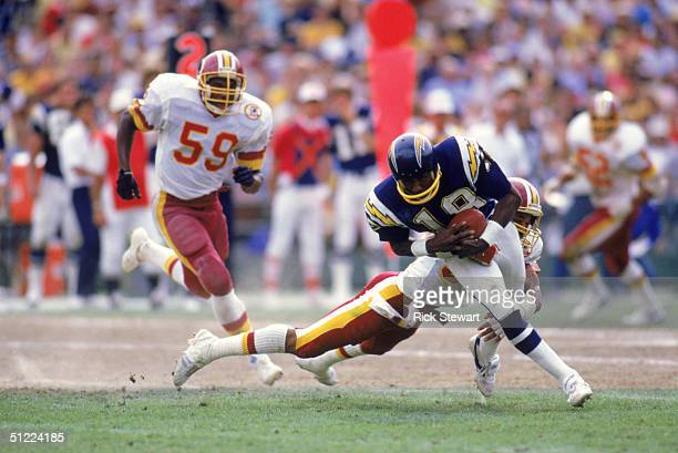 Wide receiver Charlie Joiner of the San Diego Chargers runs with the ball as he is being tackled from behind during a game against the Washington...