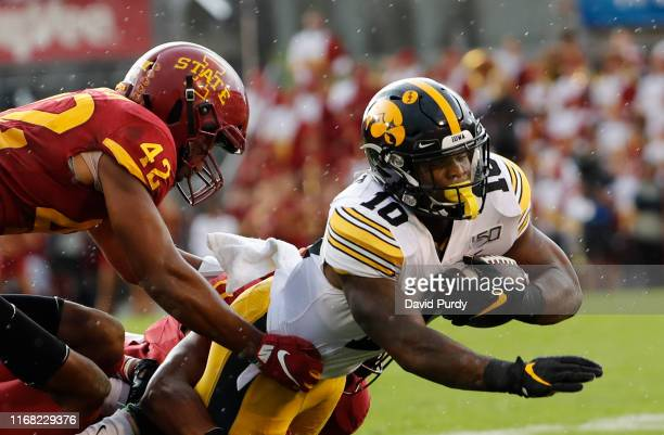 Wide receiver Charlie Jones of the Iowa Hawkeyes is tackled by linebacker Marcel Spears Jr. #42, and defensive back Lawrence White of the Iowa State...