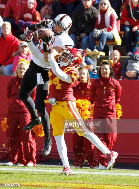 Wide receiver Charlie Moore of the Oklahoma State Cowboys pulls in a pass for a touchdown as defensive back Nigel Tribune of the Iowa State Cyclones...