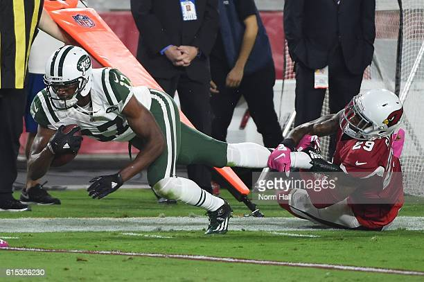 Wide receiver Charone Peake of the New York Jets is tackled by cornerback Tharold Simon of the Arizona Cardinals after a reception in the first half...