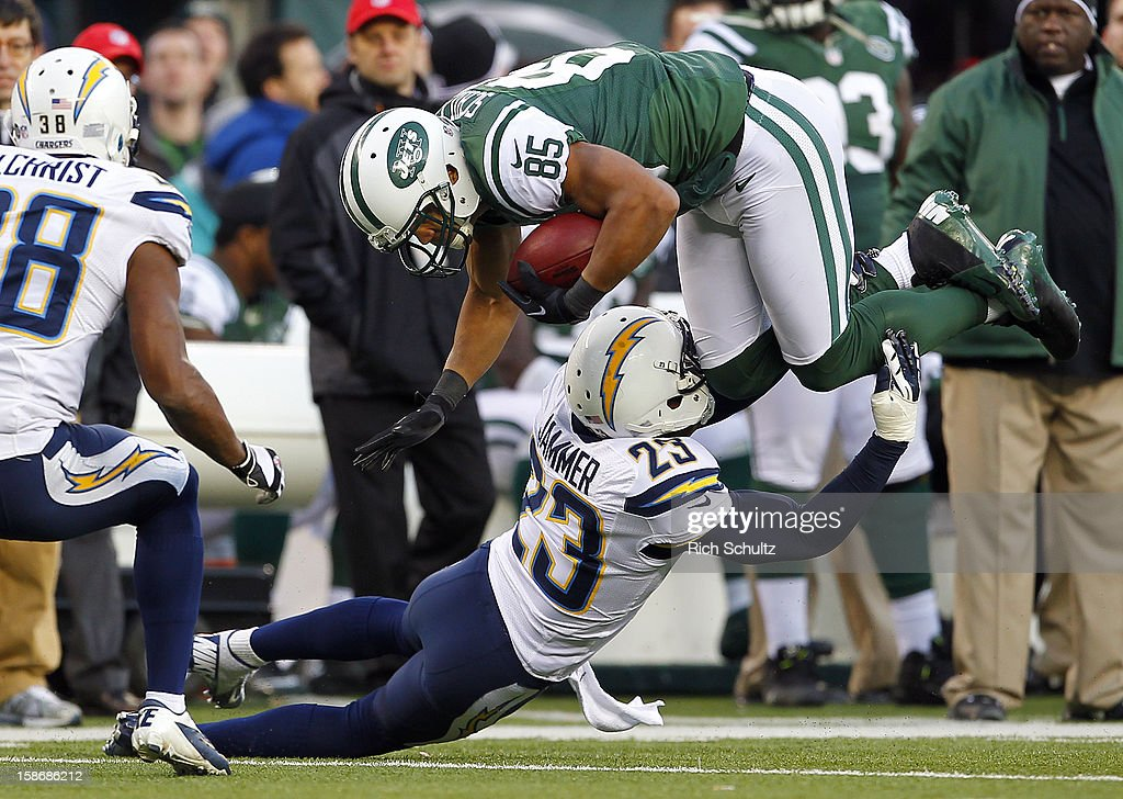 Wide receiver Chaz Schilens #85 of the New York Jets is tackled by Quentin Jammer #23 of the San Diego Chargers during the second half at MetLife Stadium on December 23, 2012 in East Rutherford, New Jersey. The Chargers defeated the Jets 27-17.