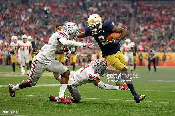 Wide receiver Chris Brown of the Notre Dame Fighting Irish is hit by safety Vonn Bell of the Ohio State Buckeyes and cornerback Eli Apple during the...