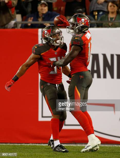 Wide receiver Chris Godwin of the Tampa Bay Buccaneers celebrates what would be the gamewinning touchdown with running back Charles Sims during the...
