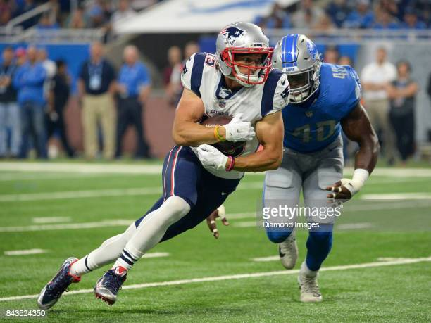 Wide receiver Chris Hogan of the New England Patriots carries the ball as he is pursued by linebacker Jarrad Davis of the Detroit Lions in the first...