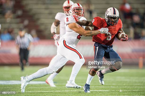 Wide receiver Chris Lewis of the South Alabama Jaguars looks to escape a tackle by safety Josh Jones of the North Carolina State Wolfpack on...