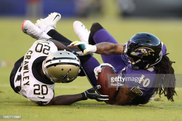 Wide Receiver Chris Moore of the Baltimore Ravens is tackled by cornerback Ken Crawley of the New Orleans Saints in the third quarter at MT Bank...