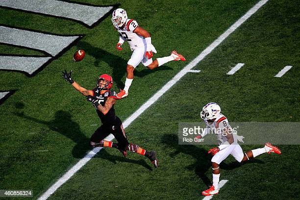 Wide receiver Chris Moore of the Cincinnati Bearcats misses a pass while being defended by Donovan Riley and safety Detrick Bonner of the Virginia...