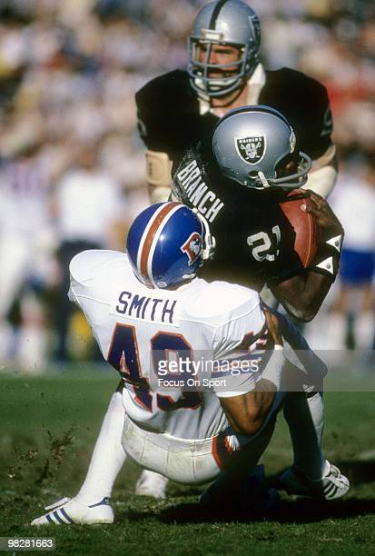 LOS ANGELES CA CIRCA 1980' Wide Receiver Cliff Branch of the Los Angeles Raiders plays is tackled by safety Dennis Smith of the Denver Broncos circa...