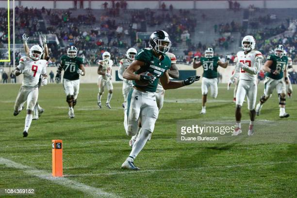 Wide receiver Cody White of the Michigan State Spartans is pursued by defensive back Saquan Hampton of the Rutgers Scarlet Knights and defensive back...