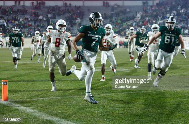 Wide receiver Cody White of the Michigan State Spartans is pursued by linebacker Tyshon Fogg of the Rutgers Scarlet Knights and defensive back Damon...