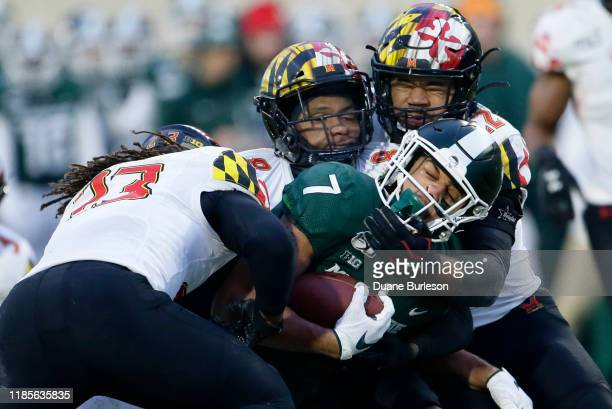 Wide receiver Cody White of the Michigan State Spartans is tackled by linebacker Fa'Najae Gotay, defensive back Marcus Lewis and linebacker Isaiah...