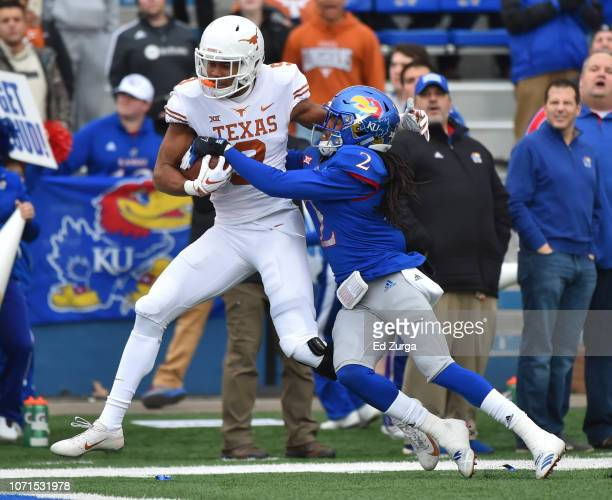 Wide receiver Collin Johnson of the Texas Longhorns goes in for a touchdown against cornerback Corione Harris of the Kansas Jayhawks in first quarter...