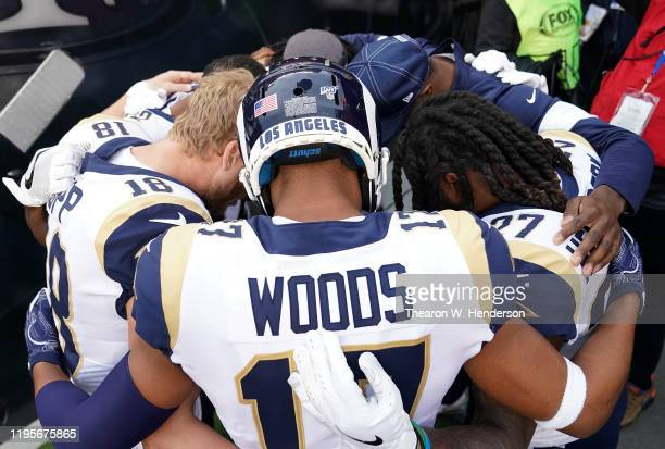 Wide receiver Cooper Kupp and Robert Woods of the Los Angeles Rams huddle with teammates with heads down before the game against the San Francisco...