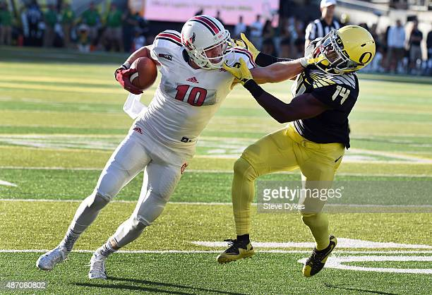 Wide receiver Cooper Kupp of the Eastern Washington Eagles stiff arms cornerback Ugo Amadi of the Oregon Ducks on the way to touchdown during the...