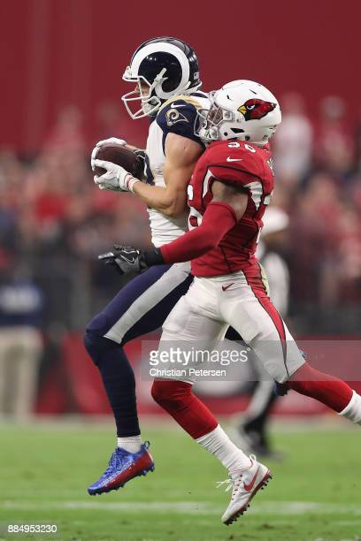 Wide receiver Cooper Kupp of the Los Angeles Rams makes a catch over safety Budda Baker of the Arizona Cardinals during the first half of the NFL...