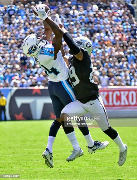 Wide receiver Corey Davis of the Tennessee Titans jumps and makes a catch against David Amerson of the Oakland Raiders during the first half at...