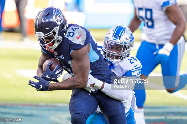 Wide receiver Corey Davis of the Tennessee Titans talks is tackled by cornerback Amani Oruwariye of the Detroit Lions at Nissan Stadium on December...