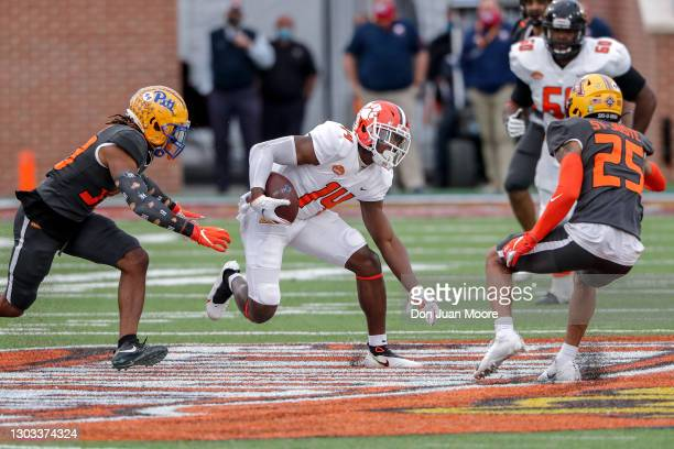 Wide Receiver Cornell Powell from Clemson of the American Team avoids being tackled by Safety Damar Hamlin from Pittsburgh and Cornerback Benjamin...