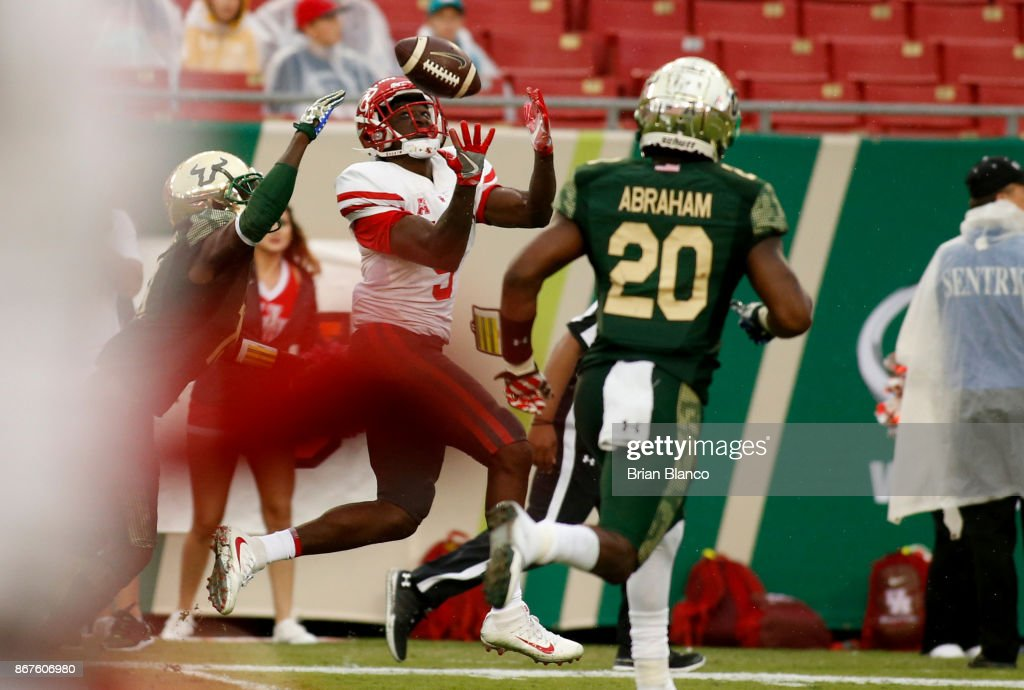 Wide receiver Courtney Lark #9 of the Houston Cougars hauls in a 39-yard touchdown pass between cornerback Ronnie Hoggins #19 of the South Florida Bulls and safety Devin Abraham #20 during the third quarter of an NCAA football game on October 28, 2017 at Raymond James Stadium in Tampa, Florida.