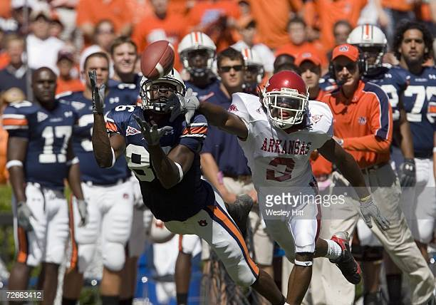 Wide receiver Courtney Taylor of the Auburn Tigers stretches out for a pass while being defended by Safety Kevin Woods of the Arkansas Razorbacks at...