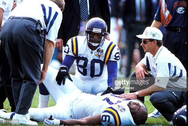 Wide receiver Cris Carter of the Minnesota Vikings consoles offensive tackle Rick Cunnungham while suffering an injury