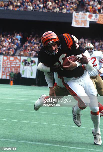 Wide Receiver Cris Collinsworth of the Cincinnati Bengals gets wrapped up from behind by a San Francisco 49ers defender during an NFL football game...