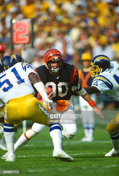Wide Receiver Cris Collinsworth of the Cincinnati Bengals looks to put a move on Pete Shaw and Woodrow Lowe of the San Diego Chargers during an NFL...