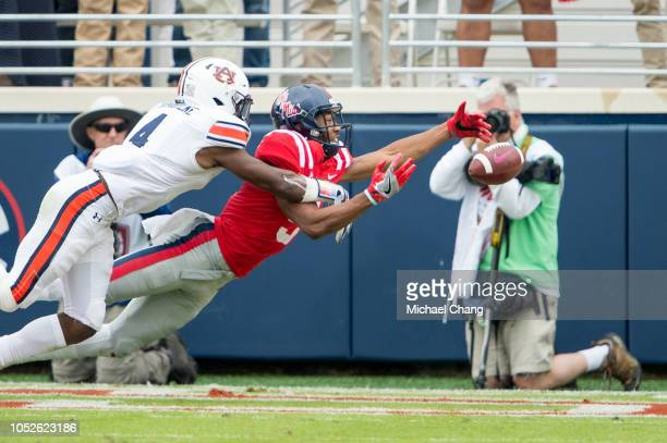Wide receiver DaMarkus Lodge of the Mississippi Rebels attempts to catch a ball in front of defensive back Noah Igbinoghene of the Auburn Tigers...