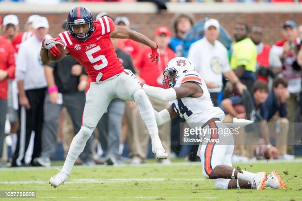 Wide receiver DaMarkus Lodge of the Mississippi Rebels looks to escape a tackle by defensive back Daniel Thomas of the Auburn Tigers at...