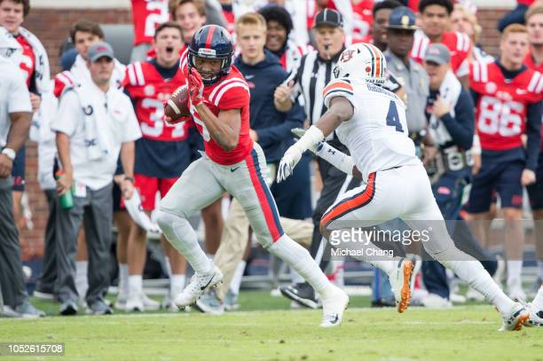 Wide receiver DaMarkus Lodge of the Mississippi Rebels runs the ball by defensive back Noah Igbinoghene of the Auburn Tigers during the second half...