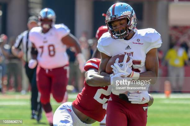 Wide receiver Damion Willis of the Troy Trojans tries to escape the tackle of defensive back Aaron Williams of the Nebraska Cornhuskers in the first...