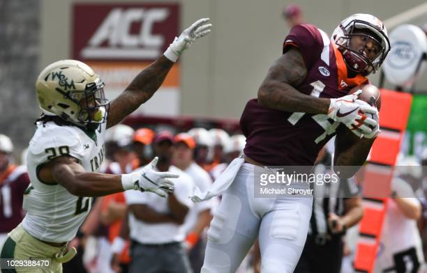 Wide receiver Damon Hazelton of the Virginia Tech Hokies makes a reception on the sideline while being defended by cornerback Raeshawn Smith of the...