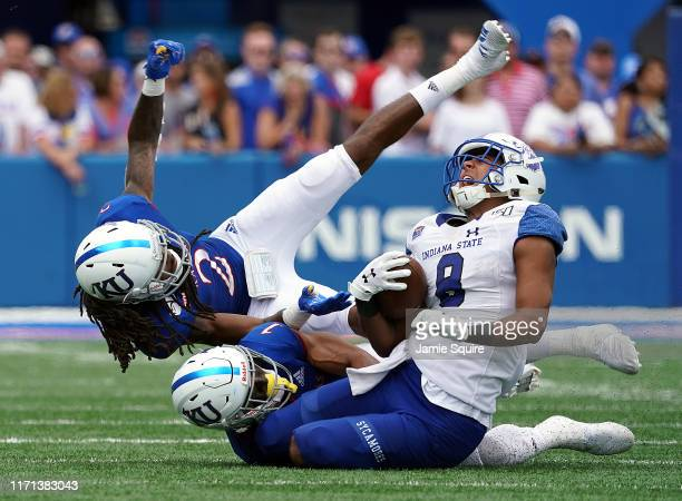 Wide receiver Dante Hendrix of the Indiana State Sycamores is tackled by safety Bryce Torneden and cornerback Corione Harris of the Kansas Jayhawks...