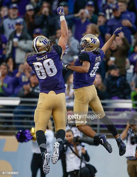 Wide receiver Dante Pettis of the Washington Huskies is congratulated by tight end Drew Sample after scoring on a 41 yard touchdown pass in the third...