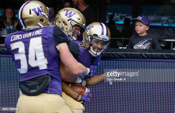 Wide receiver Dante Pettis of the Washington Huskies is congratulated by teammates after scoring on a 67yard punt return against the Montana...