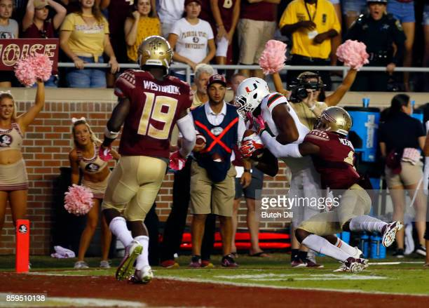 Wide receiver Darrell Langham of the Miami Hurricanes catches a pass over defensive back Tarvarus McFadden of the Florida State Seminoles for a...