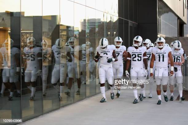 Wide receiver Darrell Stewart Jr. #25 and running back Connor Heyward of the Michigan State Spartans lead teammates out of the tunnell before the...
