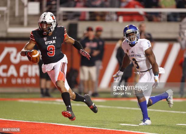 Wide receiver Darren Carrington II of the Utah Utes runs past cornerback Jermaine Kelly of the San Jose State Spartans for a touchdown during the...