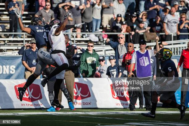 Wide receiver Darren Woods Jr #10 of the UNLV Rebels has a pass blocked by defensive back EJ Muhammad of the Nevada Wolf Pack at Mackay Stadium on...