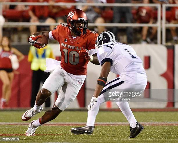 Wide receiver Darren Woods Jr #10 of the UNLV Rebels runs with the ball against defensive back Brandon Maiden of the Jackson State Tigers during...