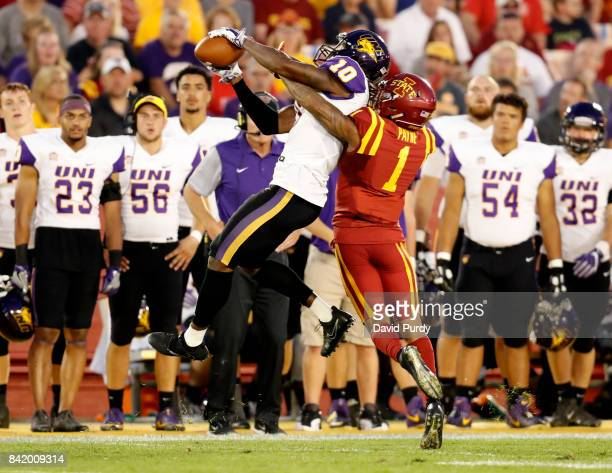 Wide receiver Daurice Fountain of the Northern Iowa Panthers pulls in a pass as defensive back D'Andre Payne of the Iowa State Cyclones blocks in the...