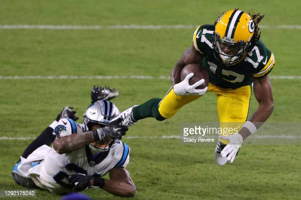 Wide receiver Davante Adams of the Green Bay Packers is bought down by outside linebacker Jeremy Chinn of the Carolina Panthers during the first...