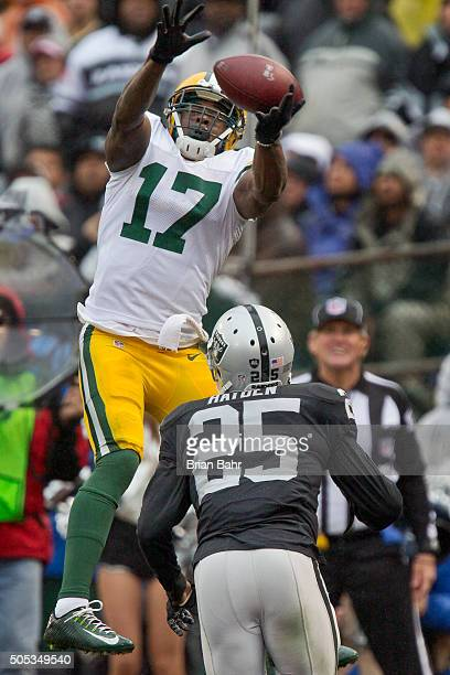 Wide receiver Davante Adams of the Green Bay Packers tries to get a handle on the ball against cornerback DJ Hayden of the Oakland Raiders in the...