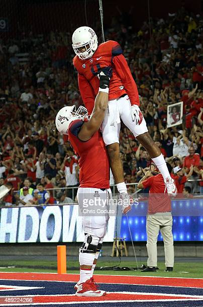 Wide receiver David Richards of the Arizona Wildcats celebrates his second quarter touchdown with offensive lineman Freddie Tagaloa during the...