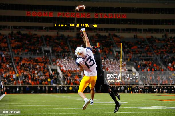 Wide receiver David Sills V of the West Virginia Mountaineers can't reach a pass over his head under coverage from cornerback AJ Green of the...