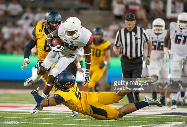 Wide receiver Davonte' Neal of the Arizona Wildcats holds on to the catch while being tackled by safety Michael Lowe of the California Golden Bears...